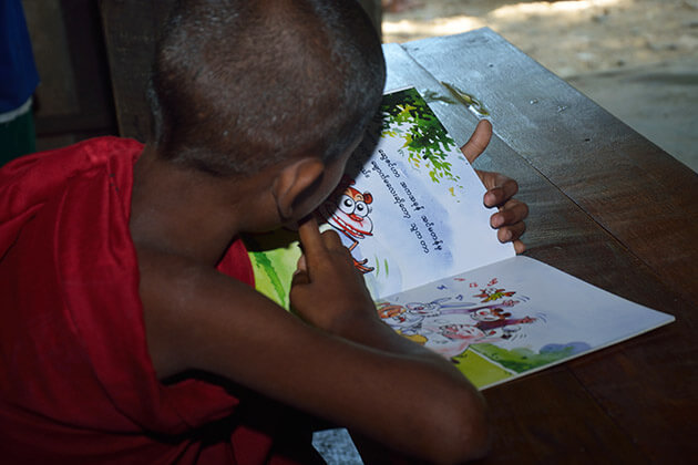 Boy reading from one of the books. Photo credit: The Benevolent Youth/The Myanmar Storytellers