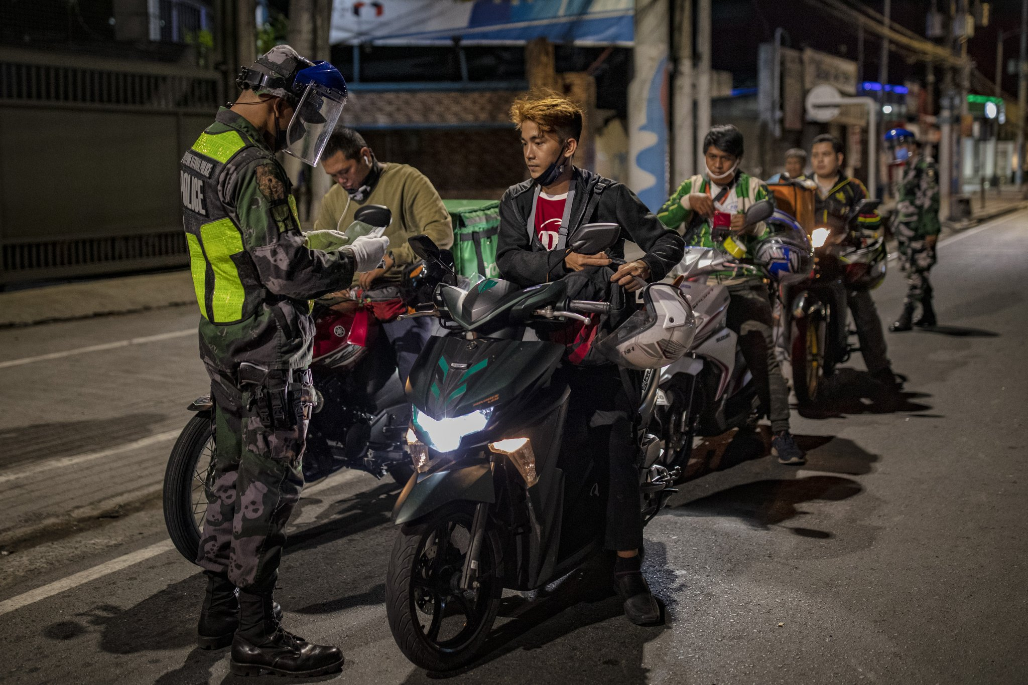 Policeman stops a line of people on motorcycles at a checkpoint in the Philippines