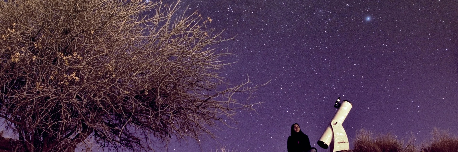 Woman with telescope looking up at the night sky. Still from the film Sapideh