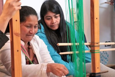 Two women sitting at a loom